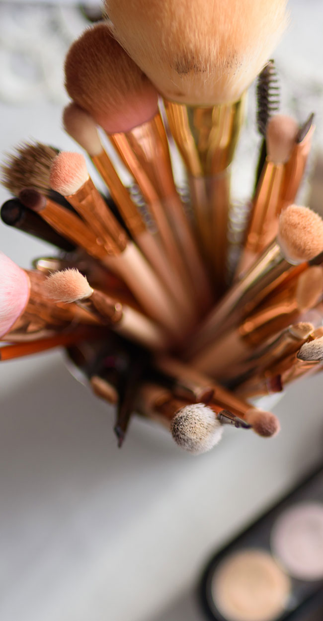 Austin Tx Makeup Services, A cup full of makeup brushes standing on end